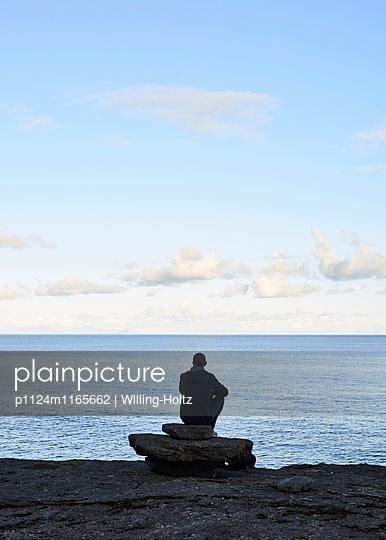 Mann blickt in die Ferne am Meer - p1124m1165662 von Willing-Holtz