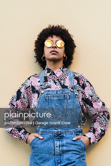 Cool young woman in dungarees and sunglasses standing in front of wall, portrait - p429m2091294 by Garage Island Crew