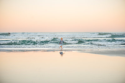Young boy running at beach in New Zealand at dusk - p1166m2130477 by Cavan Images