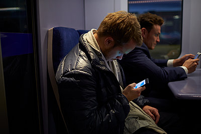 Man Sitting In Train Carriage Sending Text Message - p1407m1507334 by Monkey_Images