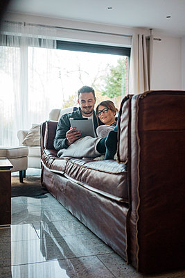 Smiling couple lying on couch at home sharing tablet - p300m1535486 by Robijn Page