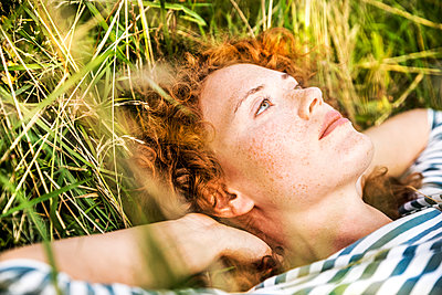 Portrait of young woman relaxing on a meadow - p300m2029022 by Jo Kirchherr