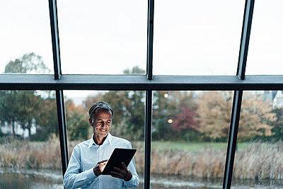 Smiling senior business professional using digital tablet against glass window - p300m2266314 by Gustafsson