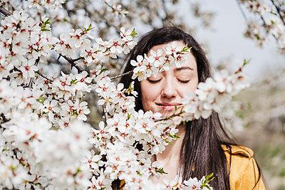 Beautiful woman seen through white flowers during springtime - p300m2274076 by Eva Blanco