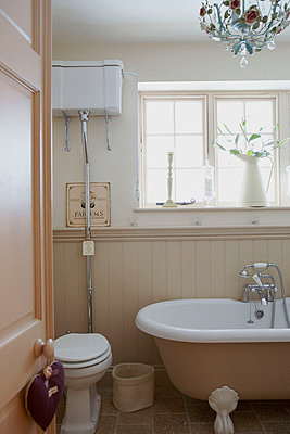 Wall mounted cistern in sunlit panelled bathroom - p349m789785 by Brent Darby