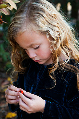 Close up of girl examining berry outdoors - p555m1409546 by Shestock