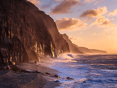 Spray from a storm blows up the cliffs at dawn in the seaside town of Sidmouth, Devon, England, United Kingdom - p871m2114102 by Baxter Bradford