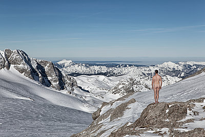 A man stands naked on a glacier and looks into the distance - p1383m2020742 by Wolfgang Steiner