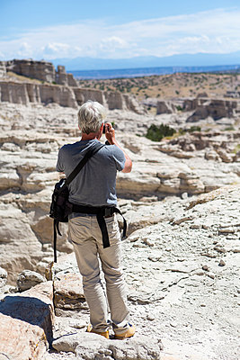 Older Caucasian man photographing rock formations, Abiquiu, New Mexico, United States - p555m1421253 by Marc Romanelli