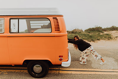Young woman pushing recreational vehicle at coastal roadside, Jalama, California, USA - p924m2068237 by Peter Amend