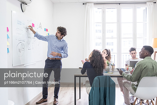 Happy people during a meeting presentation - p1166m2107764 by Cavan Images