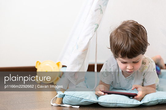 Top view of child playing in gadget - p1166m2292662 by Cavan Images