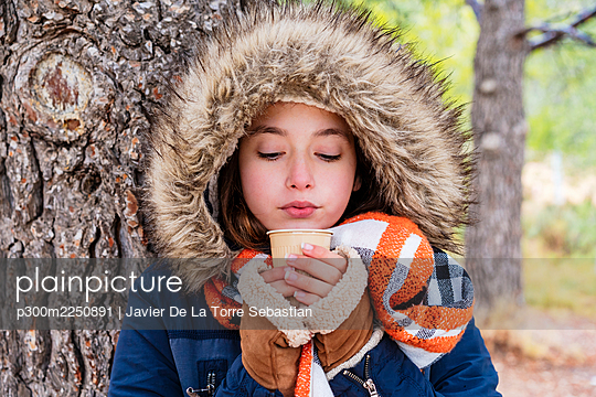 Close-up of girl wearing fur coat holding coffee in forest - p300m2250891 by Javier De La Torre Sebastian
