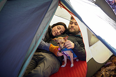 Couple with dog relaxing in tent - p1166m1231447 by Cavan Images