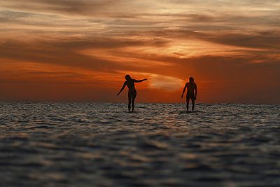 Two surfers in ocean at sunset - p1166m2137254 by Cavan Images