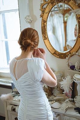 Young bride in wedding dress wearing earrings - p1315m1578907 by Wavebreak