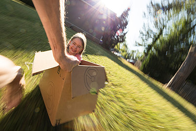 Father pulling daughter across grass in cardboard car - p1480m2229677 by Brian W. Downs
