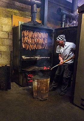 Manual worker inserting coal in smokehouse while preparing sausages at food factory - p300m2225013 by LOUIS CHRISTIAN