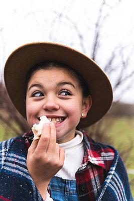 Smiling girl wearing hat eating sandwich in Autumn landscape - p300m2242773 by Josu Acosta