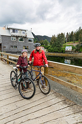 Mother and daughter with bicycles on the historic Seldovia oceanside boardwalk, Southcentral Alaska, USA - p442m1442238 by Kevin G. Smith