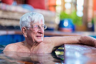 Pensive Caucasian man in swimming pool - p555m1522929 by Marc Romanelli