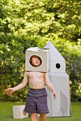 Boy Wearing Homemade Cardboard Helmet Playing in front of Rocket Spacecraft - p669m713974 by Jutta Klee photography