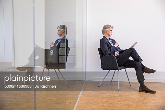 Businessman sitting on chair, using digital tablet - p300m1586983 von Jo Kirchherr