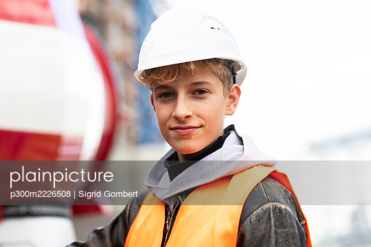 Confident male teenage trainee wearing hardhat and reflective clothing at construction site - p300m2226508 by Sigrid Gombert