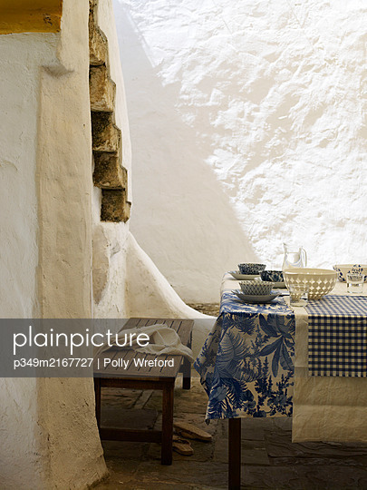Blue and white tablecloths in whitewashed courtyard exterior, Spain - p349m2167727 by Polly Wreford