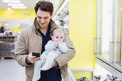 Father with baby daughter checking smart phone, shopping in supermarket - p1023m2187678 by Sam Edwards