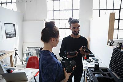 Photographers examining camera lens equipment in art studio - p1192m1490282 by Hero Images