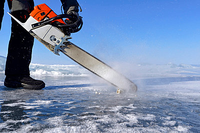 Russia, Lake Baikal, man opening an ice hole with a motor saw for ice diving - p300m1053134f by Gerald Nowak