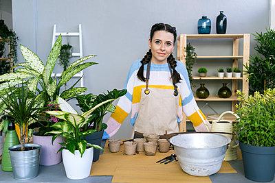 Young woman working in a gardening laboratory or plant shop - p300m2274605 von Giorgio Fochesato