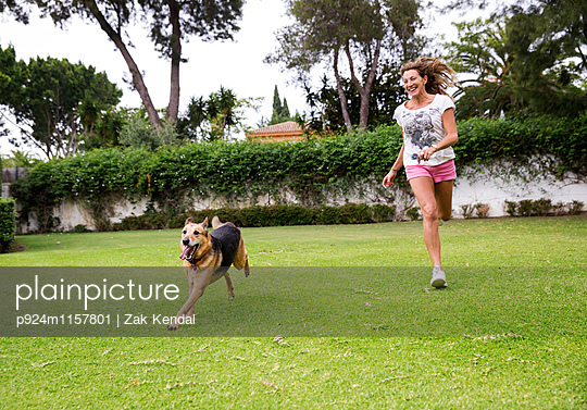 Mature woman running in park with dog - p924m1157801 by Zak Kendal