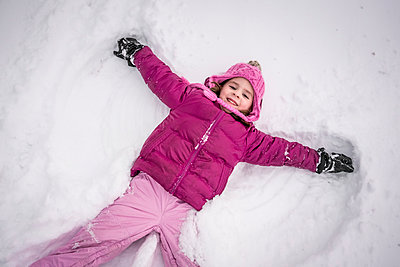 High angle portrait of happy girl making snow angel on field - p1166m2011507 by Cavan Images