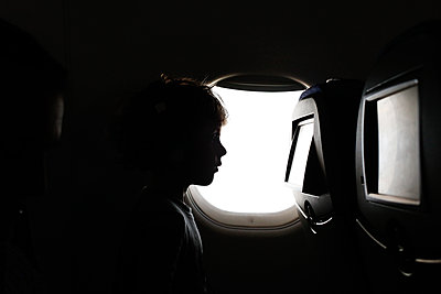 Little boy sitting on the plane watching a movie - p1166m2153338 by Cavan Images