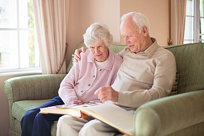 Older Caucasian couple looking at photo album - p555m1305759 by Resolution Productions