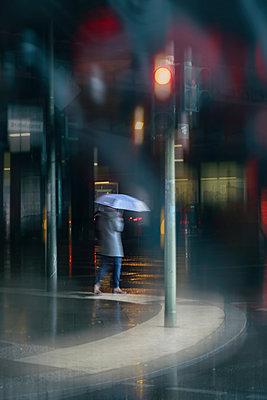 Woman crosses street in the rain - p739m2007931 by Baertels