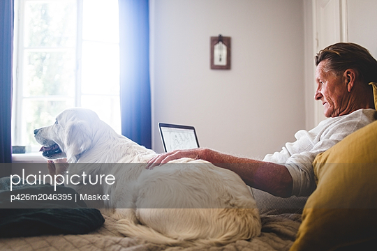 Senior man using laptop while leaning besides dog on bed at home - p426m2046395 by Maskot
