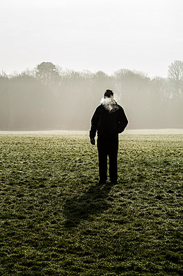 Silhouette of man standing in a field exhaling on a cold morning - p1047m1007777 by Sally Mundy