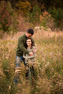 Father kissing on daughter's head while standing amidst plants in forest - p1166m2034625 by Cavan Images