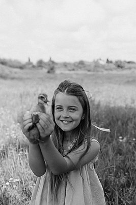 Toddler boy and girl play with the ducklings at the farm - p1166m2297309 by Cavan Images