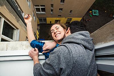 Pärchen lehnt sich aus einem Fenster und lacht glücklich  - p1301m1424730 von Delia Baum