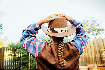 Mixed race girl wearing cowboy costume in backyard - p555m1412565 by Inti St Clair photography