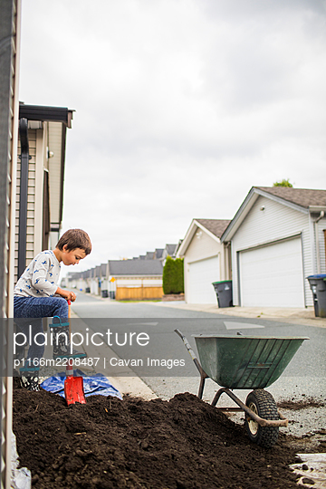 Young boy shoveling dirt into wheelbarrow in back alley - p1166m2208487 by Cavan Images