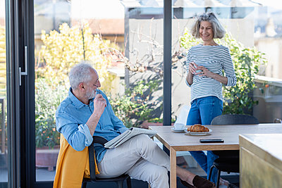 Senior man with newspaper sitting by table with woman standing in background at home - p300m2265851 by Emma Innocenti