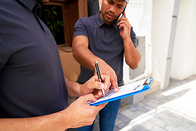 Delivery man pointing on documents held by male colleague - p300m2298710 by gpointstudio