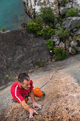 Man rock climbing on limestone rock, overhead view, Ha Long Bay, Vietnam - p429m1569725 by Alex Eggermont