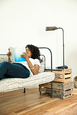 Woman lying on sofa reading book - p624m1174392 by Sigrid Olsson