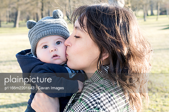 A few months old baby in a wool hat playing in his mother's arms - p1166m2201643 by Cavan Images